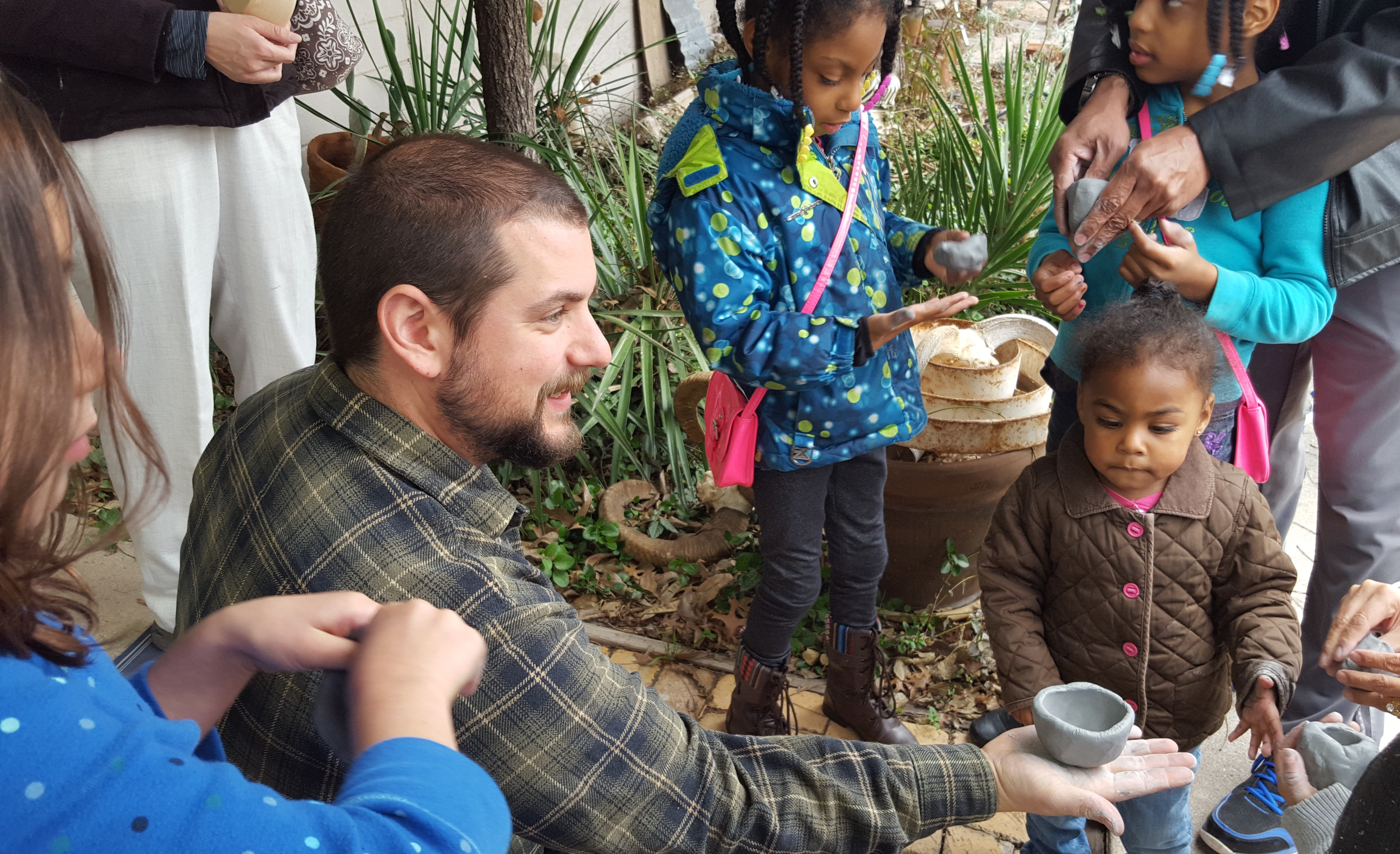 Eric Grasham showing the kids how to make a pinch pot