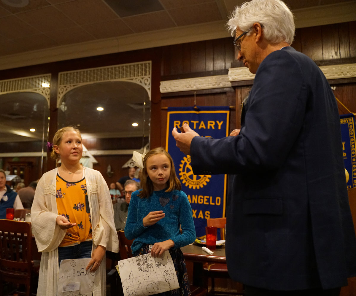 Jordon Munden and Mary Cathryn Darby receive the official Rotary coin from Rotary President Dr. Clifton Jones. (Contributed/Lorelei Day)