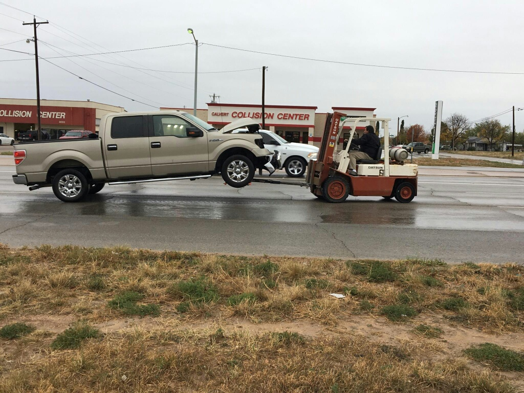 Forklift moving F150 from crash to Calvert Collision.
