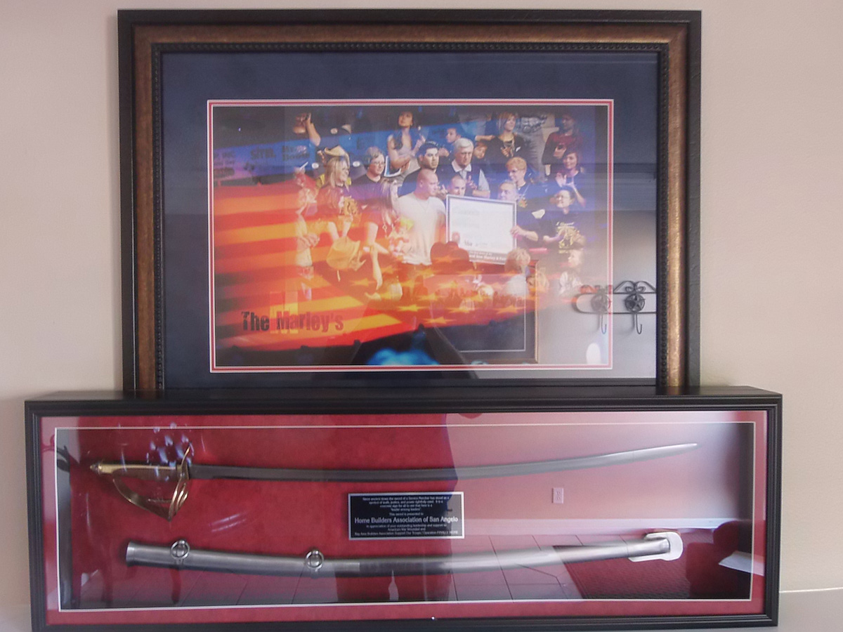 Finally Home commemorative saber and pictures at Clark Construction.