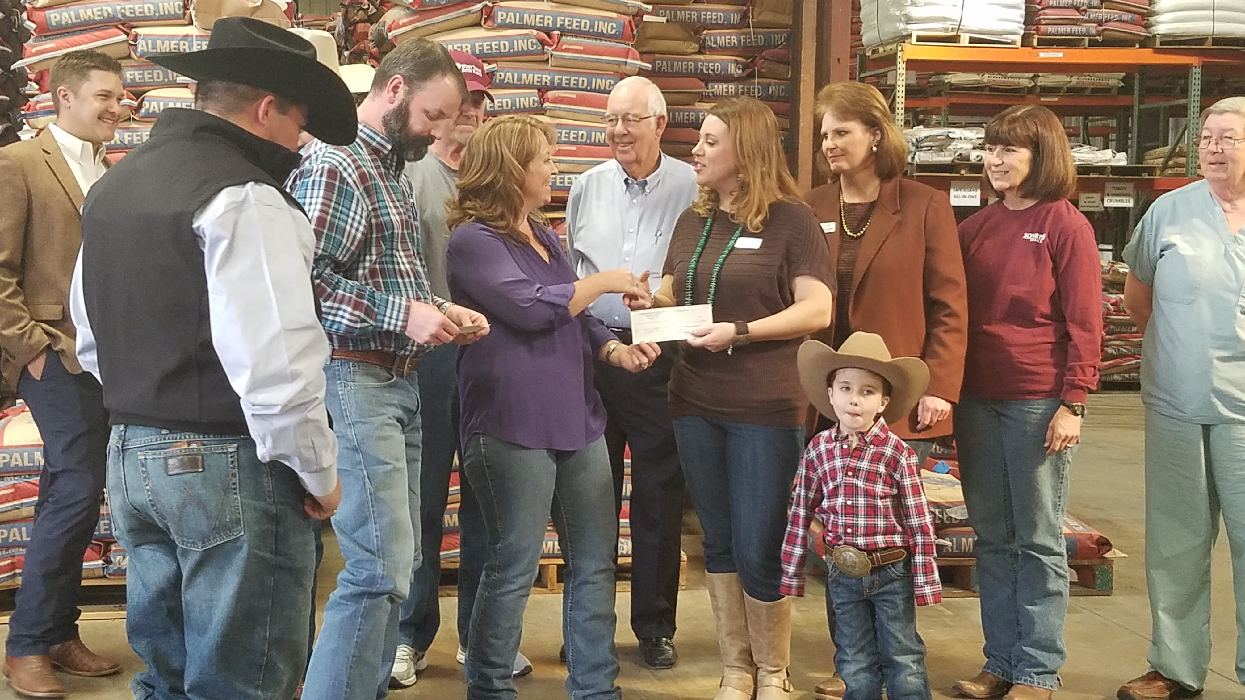 Megan Kirkwood accepts a donation check from Palmer Feed on behalf of Sonrisas Trails