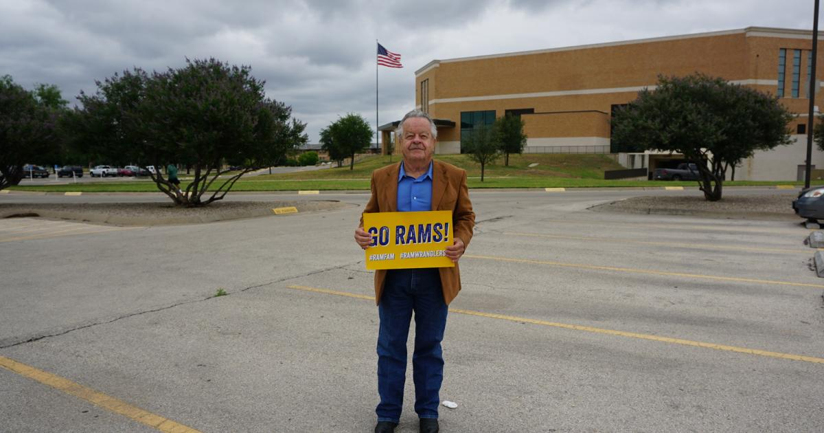 Joe Atkenson, 71, holds a sign supporting the Rambelles. (LIVE! Photo/Cameron Niblock)