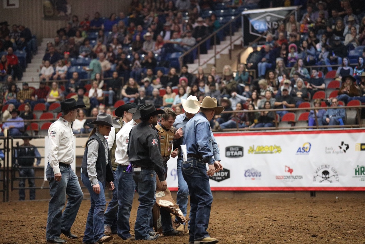 Saddle bronc rider Cody DeMoss walks off the arena floor after being knocked unconscious when getting bucked off his horse right after the buzzer. (LIVE! Photo/Shawn Morrow)