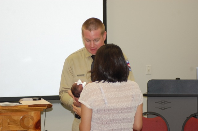 Leah Neely pins the badge on her husband Justin